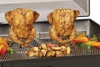 Two chickens being slowed cooked on a grill.