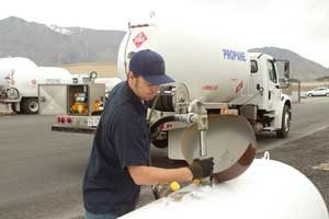 Propane technician pumping fuel into a tank