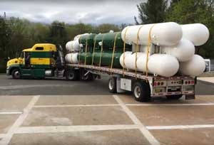 Semi truck dropping off horizontal tanks.