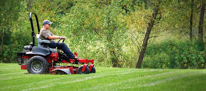 Man mowing a lawn with a commercial mower