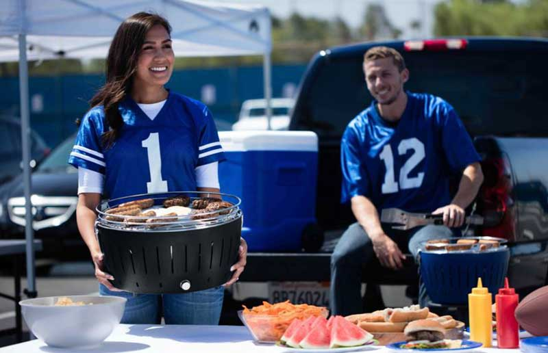Woman carrying a grill while tailgating.